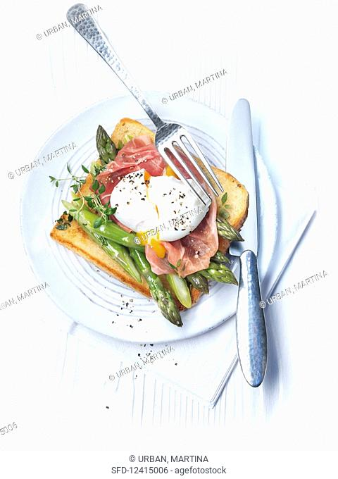 A poached egg on post with Parma ham and green asparagus