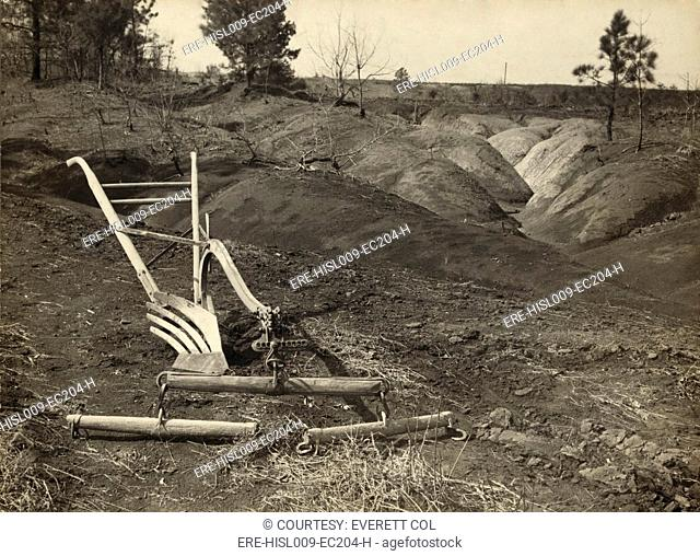 An idle plow on farm land adjacent to eroded land in Jackson County Alabama. The New Deal established agricultural education programs to teach farmers to avoid...