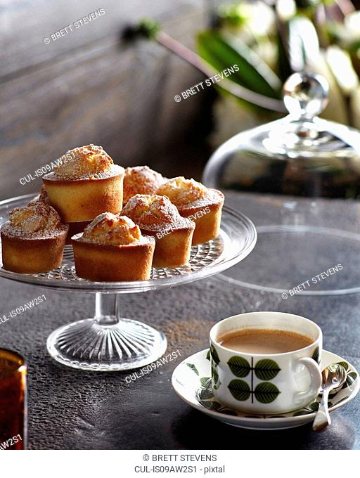 Cupcakes of cake stand with cup of tea on table