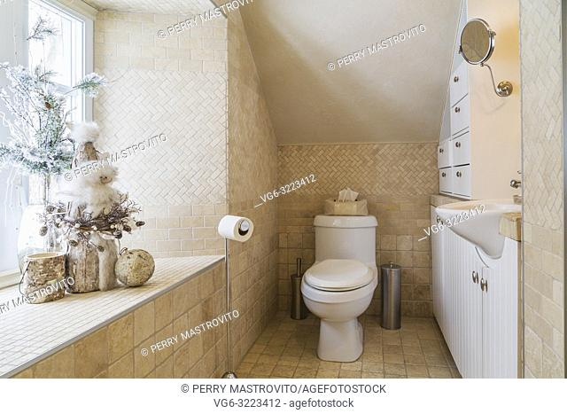 Main bathroom with travertine tile floor on the upstairs floor inside an old renovated circa 1840 Canadiana cottage style home