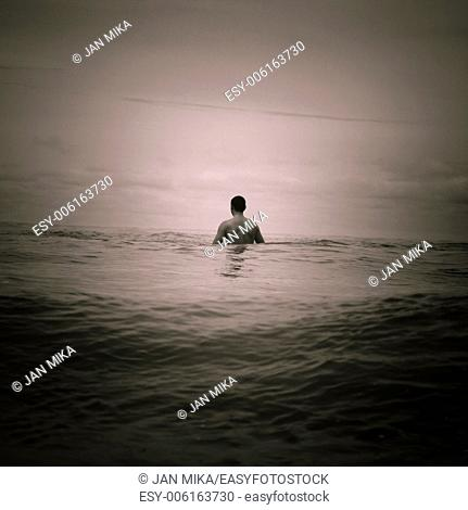 Abstract toned photo of man in the sea