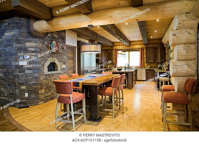 Reclaimed barn wood table with orange cloth upholstered high chairs and natural stone pizza oven in kitchen with cork floor inside a luxurious Scandinavian log...