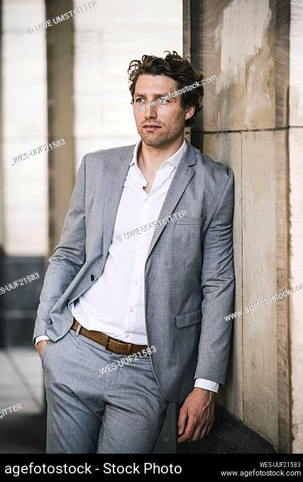 Thoughtful businessman standing while leaning on pillar in city