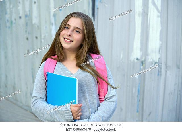Blond kid student girl back to school with notebook and backpack in the city