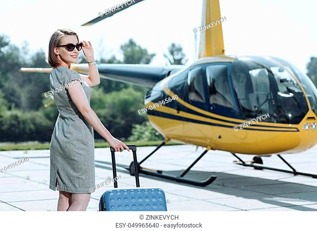 All packed. Beautiful young businesswoman carrying her luggage to helicopter, being ready for departure