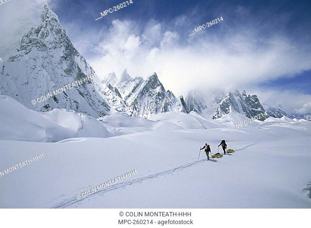 Two skiers pulling sleds under Mitre Peak, Godwin Austen Glacier, Karakoram Mountains, Pakistan