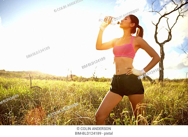 Japanese woman drinking water in rural field