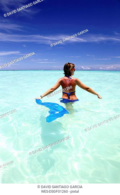 Maldives, woman standing in shallow water