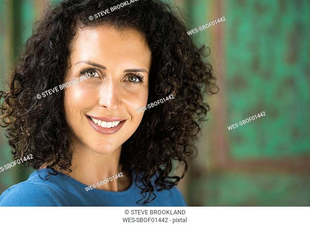 Portrait of smiling woman with curly hair