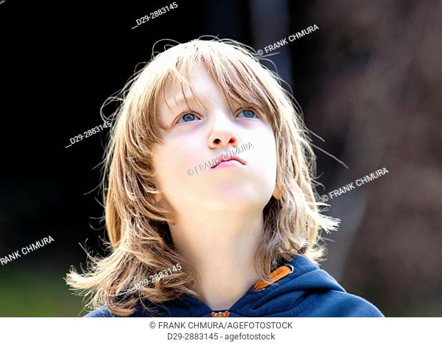 Portrait of a Boy with Long Blond Hair Outdoors