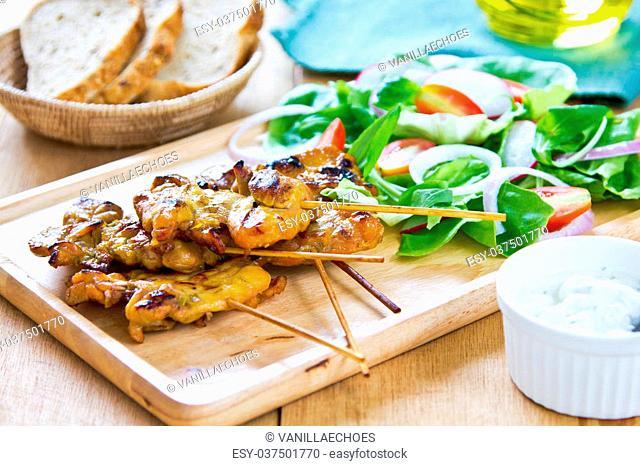 Grilled chicken skewer with salad and yogurt sauce