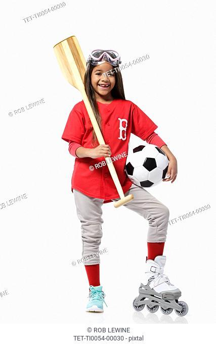 Girl dressed in baseball uniform holding sports equipment