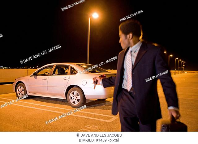 African businessman locking car in parking lot