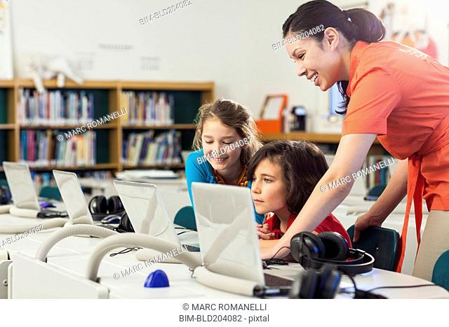 Teacher and children using laptop in library