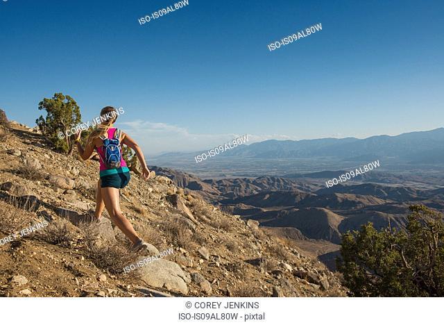 Woman running on mountain, Joshua Tree National Park, California, US