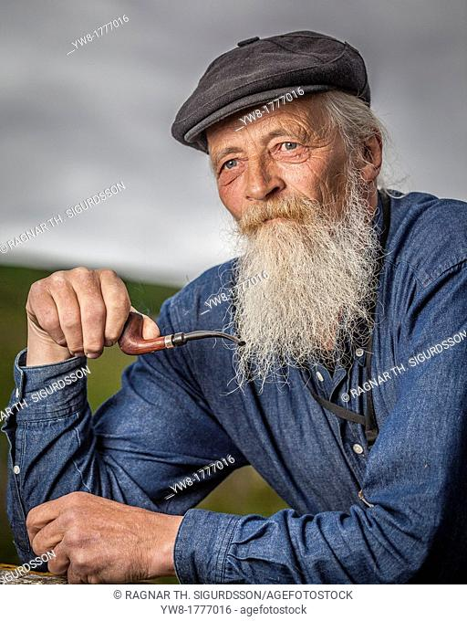 Portait of senior man with beard smoking a pipe