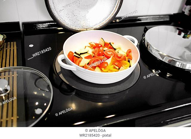 Chopped vegetables in cooking pan on stove