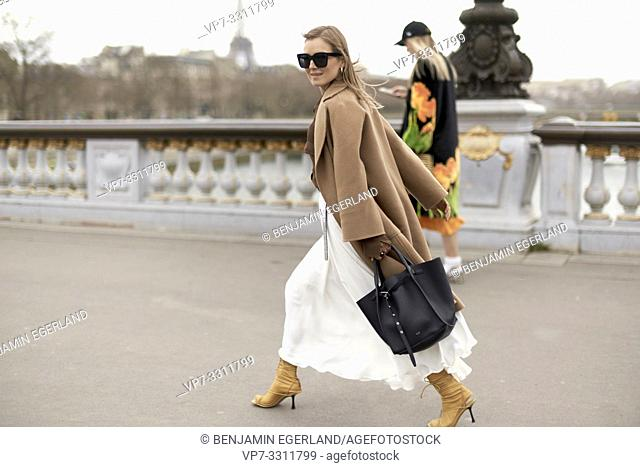 fashionable blogger woman walking in city Paris, France