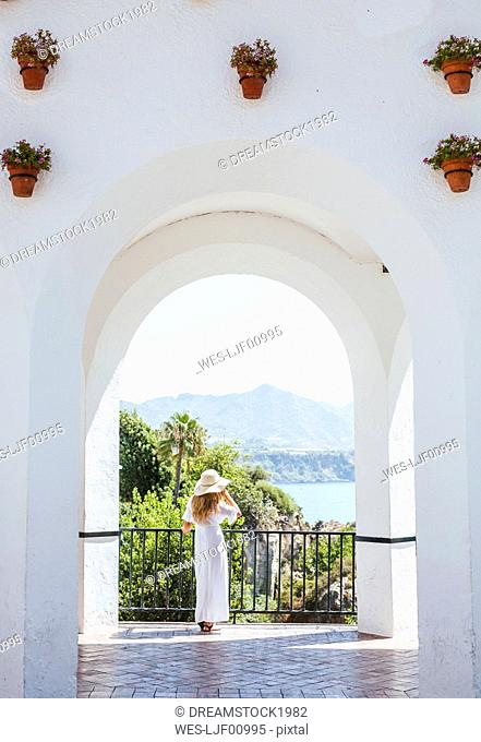 Back view of woman wearing white dress and straw hat looking at view, Nerja, Spain