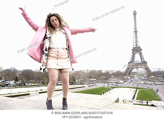 unconstrained woman dancing next to tourist sight Eiffel Tower, at Espl. du Trocadéro, in Paris, France