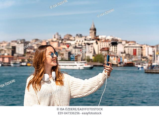 Portrait of beautiful attractive young girl with headphones and smartphone and sunglasses takes selfie with view of Galata Tower in Istanbul, Turkey