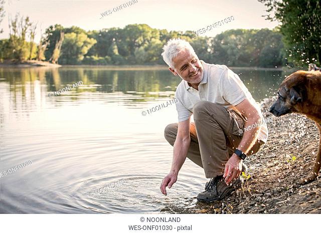 Senior man playing with dog at a lake