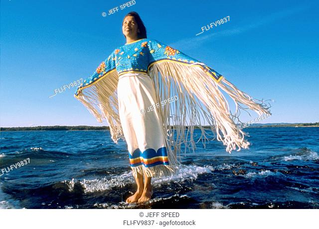Anishnawbe Woman standing on Rock in Water, Manatoulin Island, Ontario