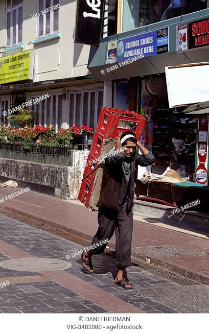 INDIA, GANGTOK, 11.11.2012, Laborer carries a heavy load of empty soda bottles through the M.G. Marg shopping area on Mahatma Gandhi Road in Gangtok, Sikkim