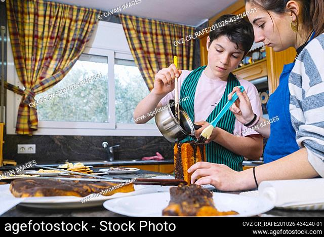 Brother and sister pouring chocolate on cake at kitchen