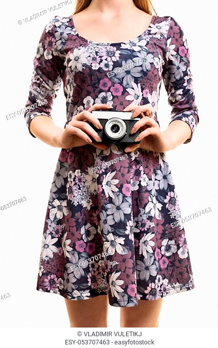 A close up shot of a girl in a colorful dress, hodling a vintage camera, isolated on white background