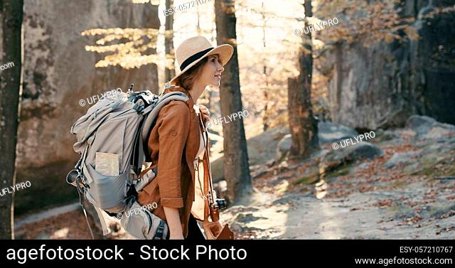 Young traveler female in a broad-brimmed hat and backpack admires the forest, looks around close-up 4k
