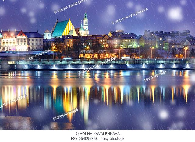Old Town with reflection in the Vistula River during snowy evening blue hour, Warsaw, Poland