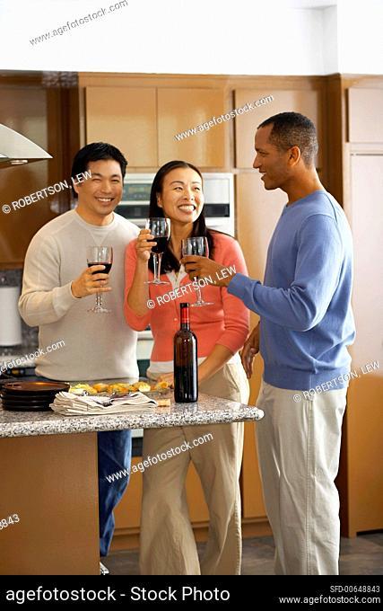 Three people drinking red wine in kitchen