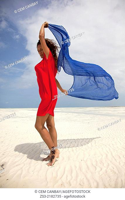 Woman with red dress on the beach, Jambiani, Zanzibar, Tanzania, East Africa