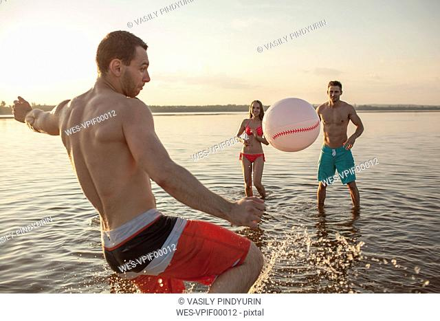 Happy friends playing with a ball in water