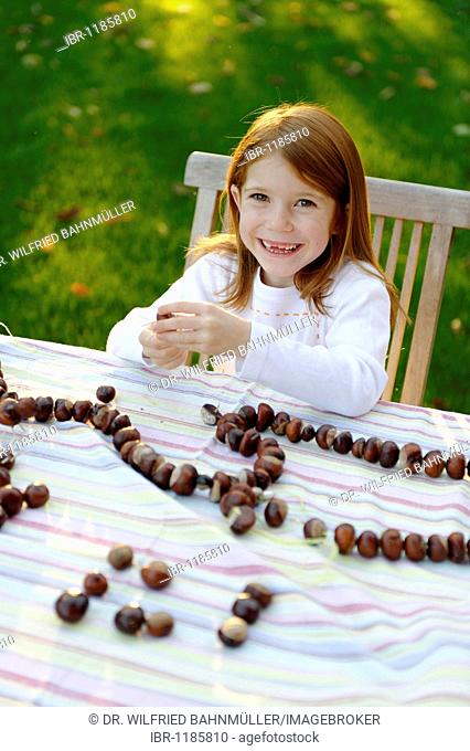 Girl is playing in the garden with chestnuts, chestnut figures