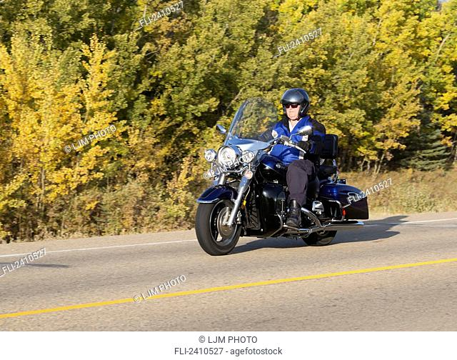 Mature man riding a motorcycle on highway; Edmonton, Alberta, Canada