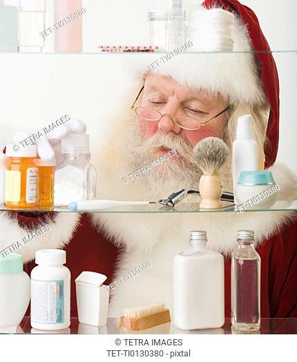 Santa Claus looking in medicine cabinet
