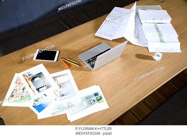 Desk with laptop, tablet, photographies and blueprint