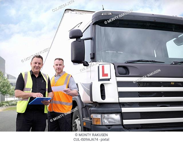 Portrait of trainee truck driver receiving pass certificate from instructor