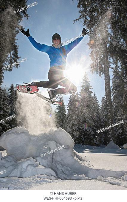Austria, Salzburg State, Altenmarkt-Zauchensee, Man with snowshoes jumping in winter landscape
