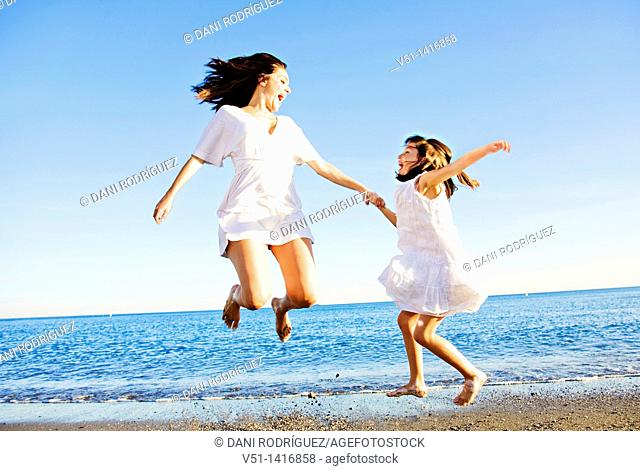 Mother and daughter jumping and having fun at the beach