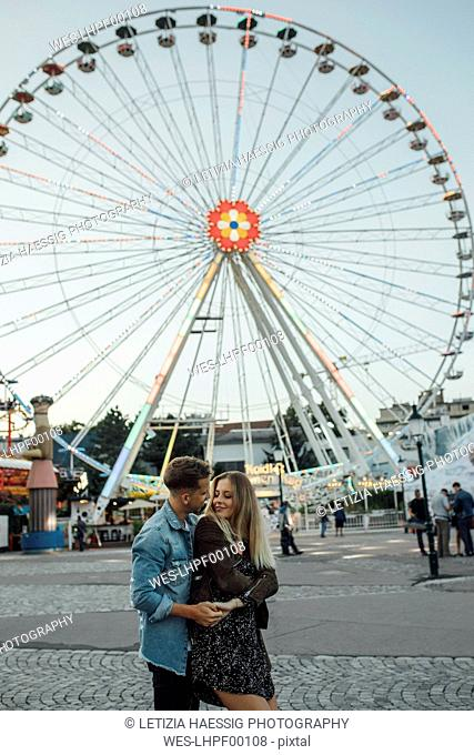 Young couple in love, embracing at a funfair