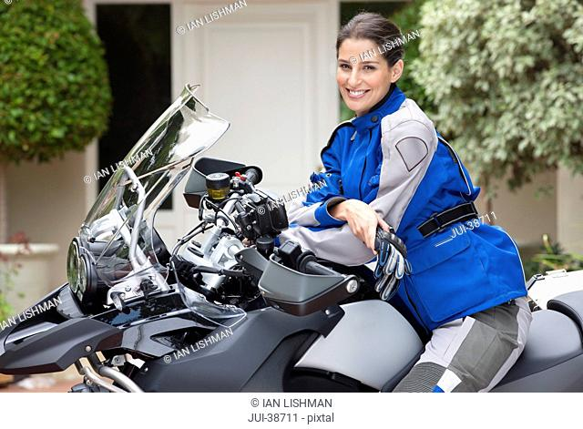 Portrait of smiling young woman on motorcycle in driveway