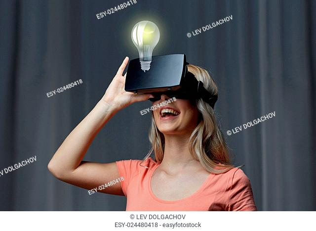technology, virtual reality, entertainment and people concept - happy young woman with virtual reality headset or 3d glasses playing game at home looking at...