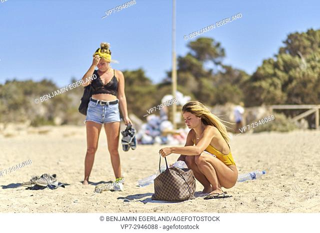 two young Dutch women on vacations packing on the beach. Dutch ethnicity. At holiday destination Chrissi Island, Crete, Greece