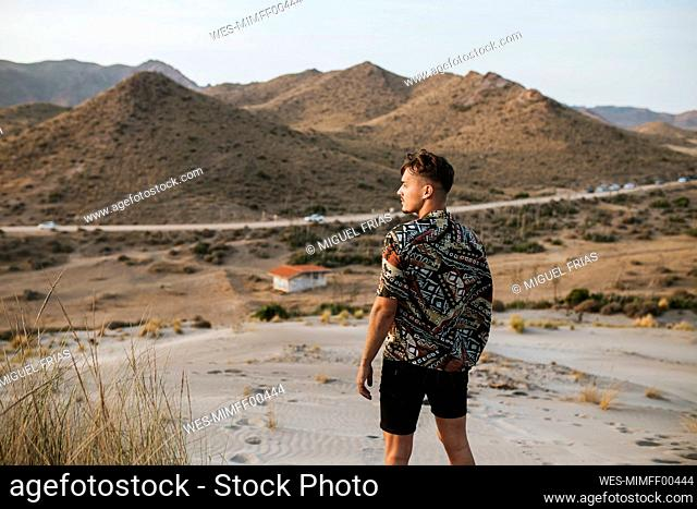 Young man standing in desert at Almeria, Tabernas, Spain