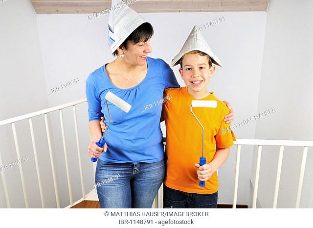Paintwork, mother and son with rollers and paper hats