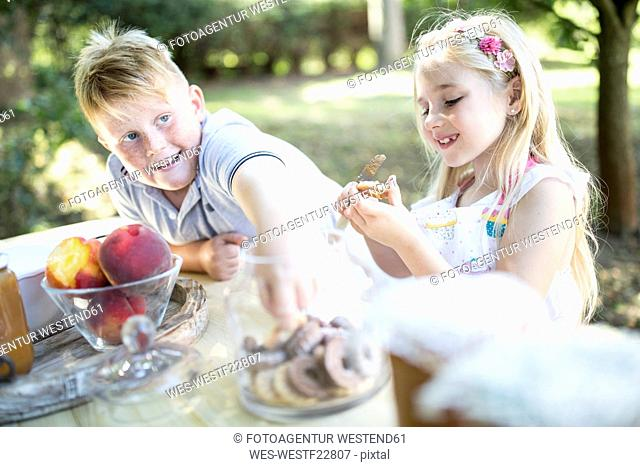 Sister and brother eating cakes at garden table