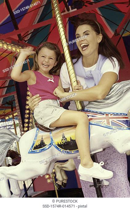 Low angle view of a daughter sitting on a carousel horse with her mother standing beside her